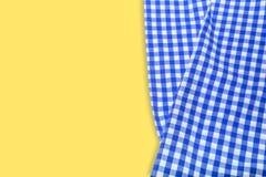 Tovagliolo a quadretti blu su un fondo giallo immagine stock