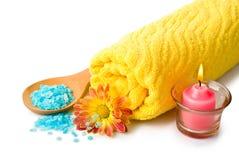 Tovagliolo, sale di bagno blu, candela e fiore Immagini Stock