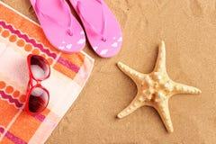 Tovagliolo, sandali, occhiali da sole e stelle marine Fotografie Stock Libere da Diritti