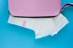 Tovagliolo sanitario in women' borsa rosa di s su fondo blu immagine stock