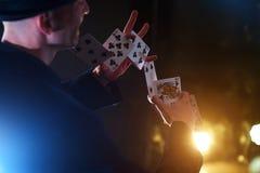 Tovenaar die truc met speelkaarten tonen Magisch of handigheid, circus, het gokken Goochelaar in donkere ruimte met mist stock foto