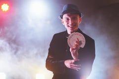 Tovenaar die truc met speelkaarten tonen Magisch of handigheid, circus, het gokken Goochelaar in donkere ruimte met mist royalty-vrije stock afbeeldingen