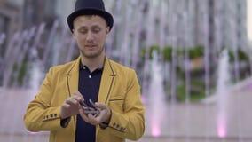 Tovenaar in geel jasje met speelkaarten in handen stock video