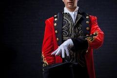 tovenaar Het close-up van dient handschoenen in de kerel in rode camisole en de cilinder stock afbeelding