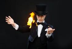 Tovenaar in hoge zijden die truc met brand tonen Stock Afbeelding