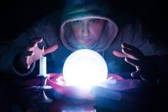 Tovenaar met magische gloeiende orb en handholding boven een glas van licht stock afbeeldingen