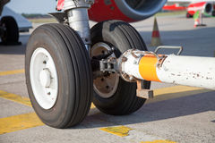 Tow bar and nosewheel. Tow bar connected to the nosewheel on an airliner Stock Images