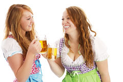 Tow bavarian girls with beer skoaling at each othe. R on white background Stock Photo