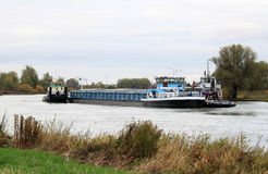 Tow boats drag rudderless freighter at dutch river Royalty Free Stock Photo