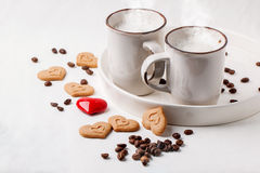 Tow cup of cappuccino with cookies as hearts Royalty Free Stock Images
