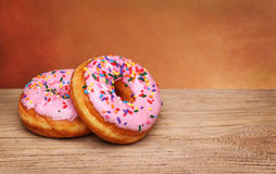 Tow Donuts with Sprinkles on wood background royalty free stock images