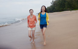 Tow girls running on the phuket beach Stock Images