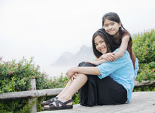 Tow girls sitting near misty ocean shore Royalty Free Stock Photography