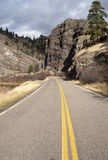 Tow Lane Highway Travels Rugged Territory Western United States. Rugged rock formations surround the road in much of the western United States Stock Photo