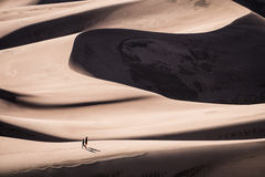 Tow Person Walking on Sand Dunes at Daytime Stock Image