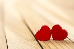Tow red wooden hearts. On wood background stock images