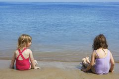 Tow sisters sit on beach bathing suit swimsuit Royalty Free Stock Photos