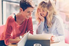 Tow smiling businesswomen making conversation at modern studio office.Handsome coworkers at working process.Horizontal. Blurred Royalty Free Stock Photo