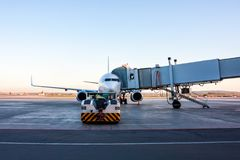 The tow tractor drive up at the passenger airplane parked to a boarding bridge. The tow tractor drive up at the passenger aircraft parked to a boarding bridge royalty free stock images