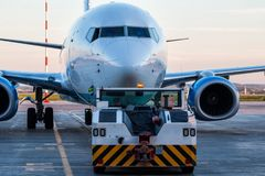 Tow tractor pushes the passenger aircraft at the airport apron. Tow tractor pushes the passenger airplane at the airport apron stock photo