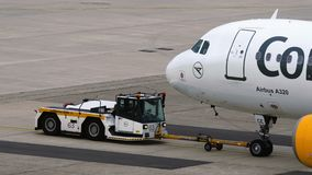 Tow tractor pushing Airbus A320 of Condor airlines