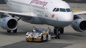 Tow tractor pushing Airbus A319 at Dusseldorf airport. DUSSELDORF, GERMANY - JULY 23, 2017: Close-up of towing tractor pushing Germanwings airbus A319 jet stock photos