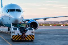 Tow tractor is pushing the passenger airplane. Tow tractor is pushing the passenger aircraft stock photography