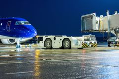 The tow tractor rolls back the passenger airplane from the air b. Ridge at the airport apron royalty free stock images