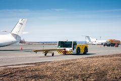 Tow tractor with towbar and tank truck aircraft refuelers moves at the airport apron. Tow tractor with towbar and tank truck airplane refuelers moves at the royalty free stock photos