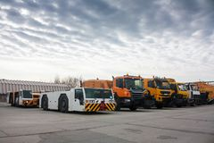 Tow tractors and cleaning trucks in the airport Stock Photography