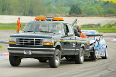 Tow truck. THRUXTON, UNITED KINGDOM - MAY 1, 2011: Ford recovery truck towing away the wreckage of a Chevrolet driven by Jason Plato during the British Touring Stock Image
