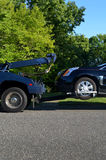 Tow Truck with Disabled Vehicle. A blue wrecker tow truck towing a black disabled SUV on a clear sunny day Royalty Free Stock Photo