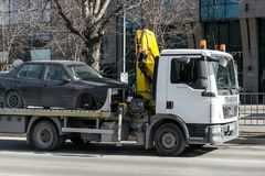 A tow truck with hook and chain transports a car without a front wheel along the city street during the day stock photo