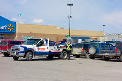 A tow-truck removing a car from a parking lot in the yukon. A broken-down vehicle in need of a tow from the walmart at whitehorse Stock Photos