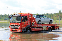 Tow Truck Rescuing Car From Flood. KARJAA, FINLAND - JULY 27, 2013: Mercedes Benz tow truck rescuing a car from flooded area in Karjaa, Finland on July 27, 2013 Royalty Free Stock Photography