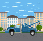 Tow truck on road in urban landscape Stock Photo