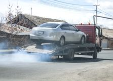 Tow truck taking away faulty car. Transport Stock Image