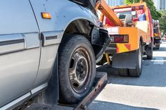 Tow truck towing a broken down car in emergency. On the street stock images