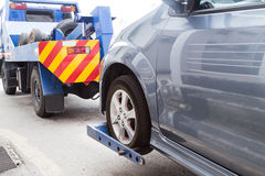 Tow truck towing a broken down car on the street.  Royalty Free Stock Image