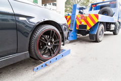 Tow truck towing a broken down car on the street. Close up of tow truck towing a broken down car with nice sports rim on the street next to commercial building royalty free stock image