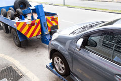 Tow truck towing a broken down car on the street Royalty Free Stock Photo