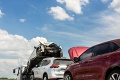 Free Tow Truck Trailer On Highway Carrying Three Damaged Cars Sold On Insurance Car Auctions For Repair And Recovery.  Vehicles Stock Photography - 145711642