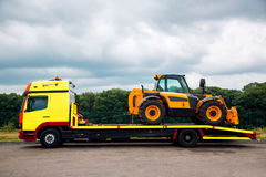 Tow truck transports new tractor. The tow truck on the platform transports the new tractor, the equipment for technical and agricultural works royalty free stock image