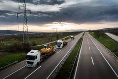 Tow Trucks die op een rij de Graafwerktuigen van Bouwmachines dragen Stock Foto