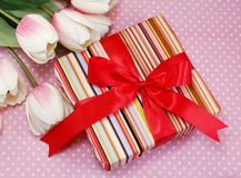 Pink gift box with bow present and tulip artificial flowers on pink polka dot background Royalty Free Stock Photo