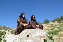 Tow women sitting on rock. Two girls sitting on a rock and looking at the summer landscape royalty free stock photos