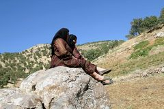 Tow women sitting on rock. Two girls sitting on a rock and looking at the summer landscape royalty free stock photo