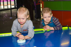 Towable play Air Hockey. Boys play at amusement Air hockey royalty free stock photo