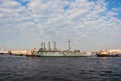 Towage de uma Aurora histotical do cruzador a um lugar do reparo na doca, St Petersburg, Rússia Imagens de Stock Royalty Free