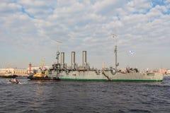 Towage de uma Aurora histotical do cruzador a um lugar do reparo na doca, St Petersburg, Rússia Fotografia de Stock Royalty Free
